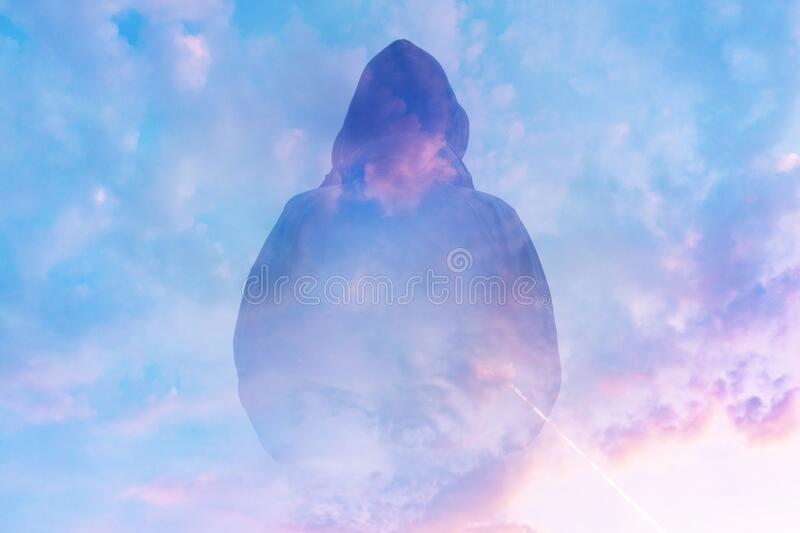 A double exposure of a moody, hooded figure silhouetted against the sunset. With an abstract, experimental dream like edit.  stock photography