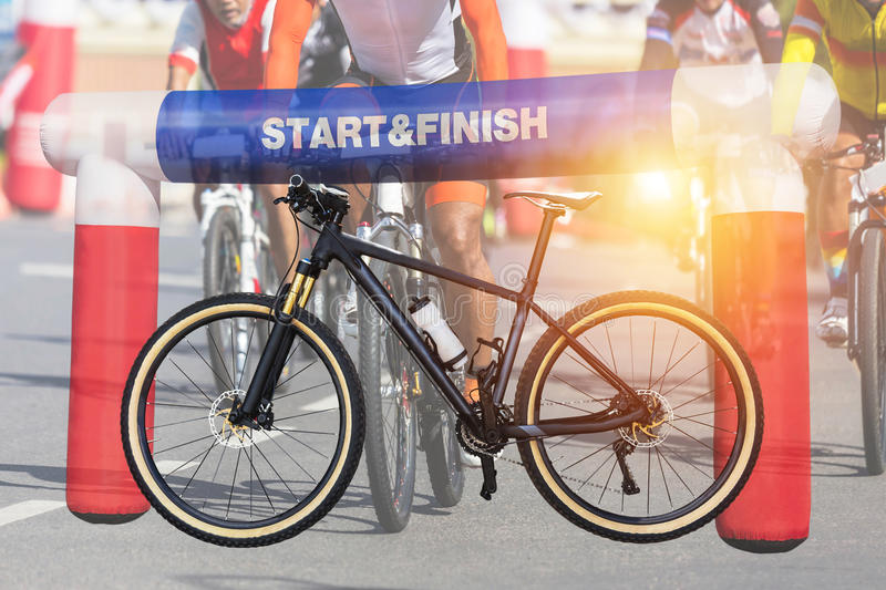 Double exposure mountain bicycle and inflatable start - finish arch with cyclists during bicycle sport racing competition royalty free stock photo