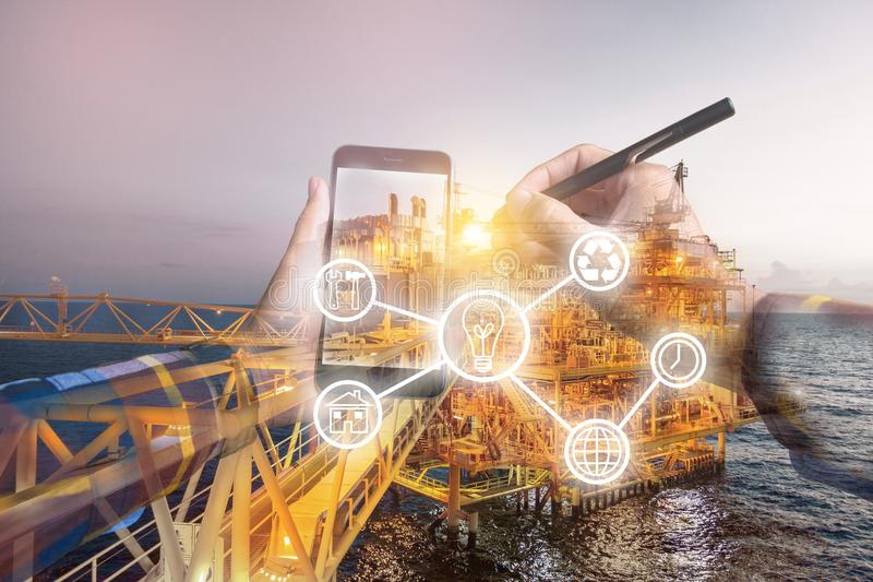 Double exposure photo, hand touching mobile phone for using business tool icons,with oil & gas platform background for stock photos