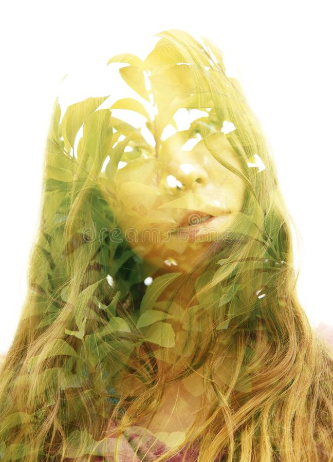 Double exposure portrait of a young natural beauty combined with tree branches and leaves. Double exposure with an ecological concept showcasing the beauty of royalty free stock photography