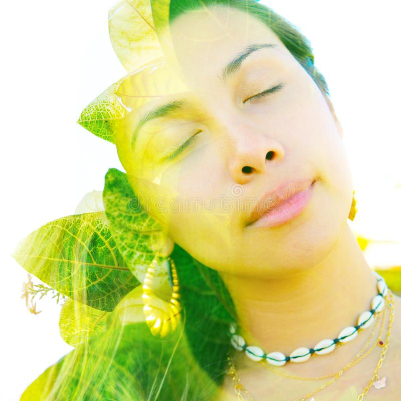 Double exposure close up portrait of a young pretty woman interwoven with bright leaves of a vibrant tropical tree royalty free stock photos