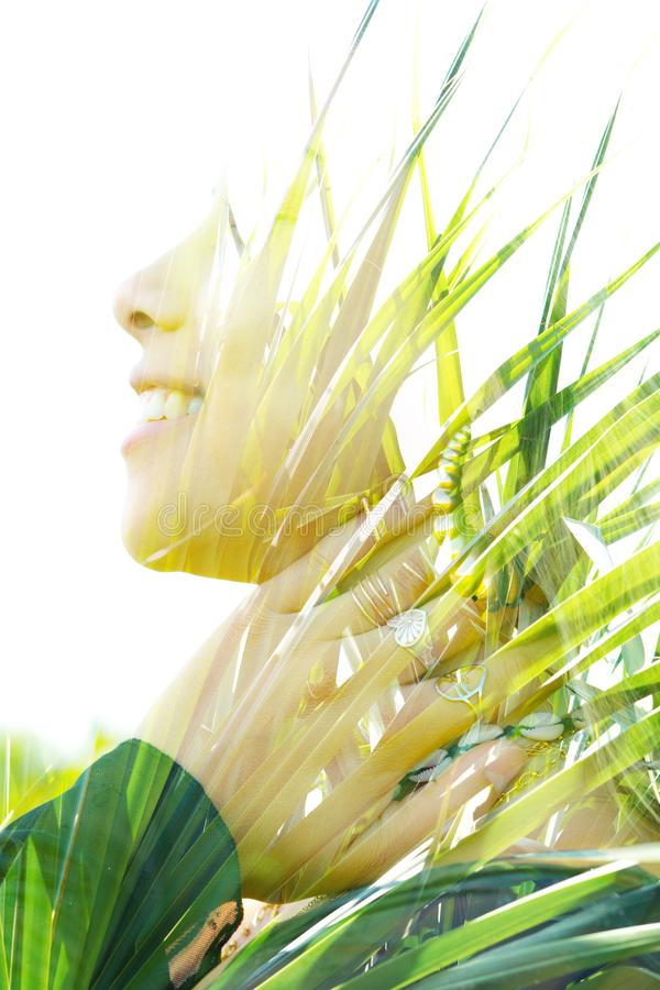 Double exposure close up portrait of a young pretty woman interwoven with bright leaves of a vibrant tropical tree royalty free stock image