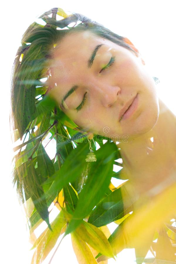 Double exposure close up portrait of a young pretty woman interwoven with bright leaves of a vibrant tropical tree stock photography