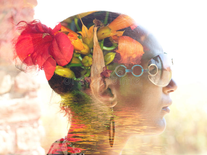 Double exposure portrait of a young woman with colorful flowers stock photo