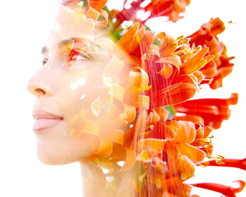 Double exposure profile of a natural beauty with lush orange flowers which seemingly grow from her hair, against a white royalty free stock photos