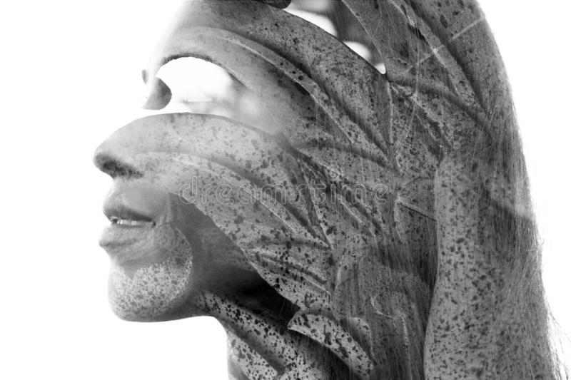 Double exposure close up portrait of an attractive young woman combined with a Balinese rock statue with leaf texture, black and. Double exposure profile stock images