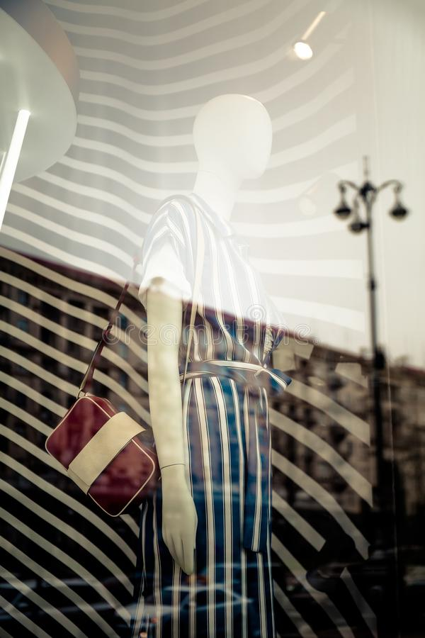 Double exposure is a reflection of the city on the glass shop window with a mannequin in fashionable clothes stock images