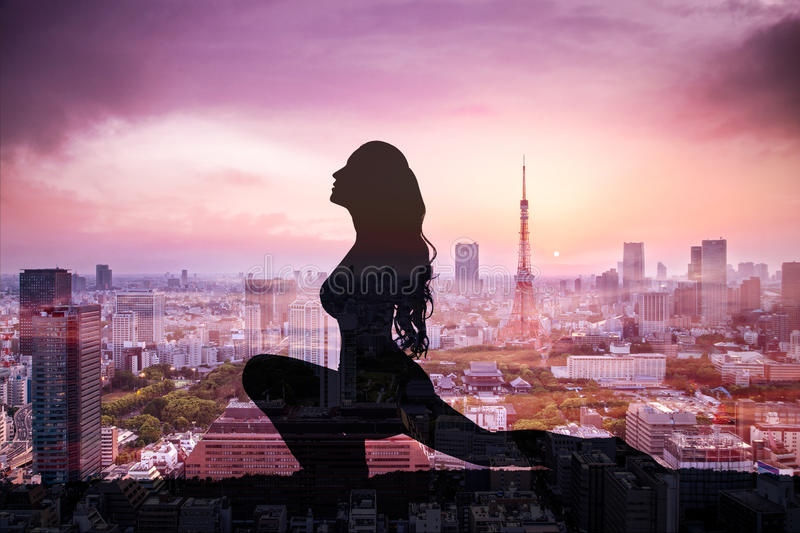 Double exposure of Silhouette yoga woman against Tokyo city royalty free stock image