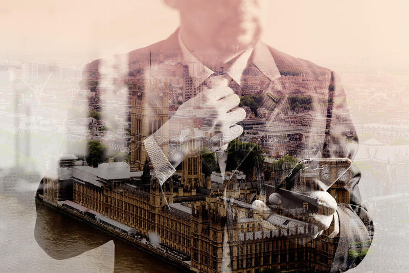 double exposure of success businessman holding tie and using smart phone,thinking,front view,filter effect,London buildings city stock images