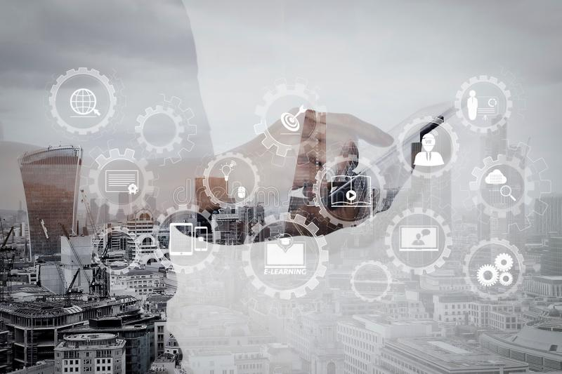 Double exposure of success businessman using digital tablet with. E-learning with connected gear cogs connected diagram virtual dashboard.Double exposure of stock image