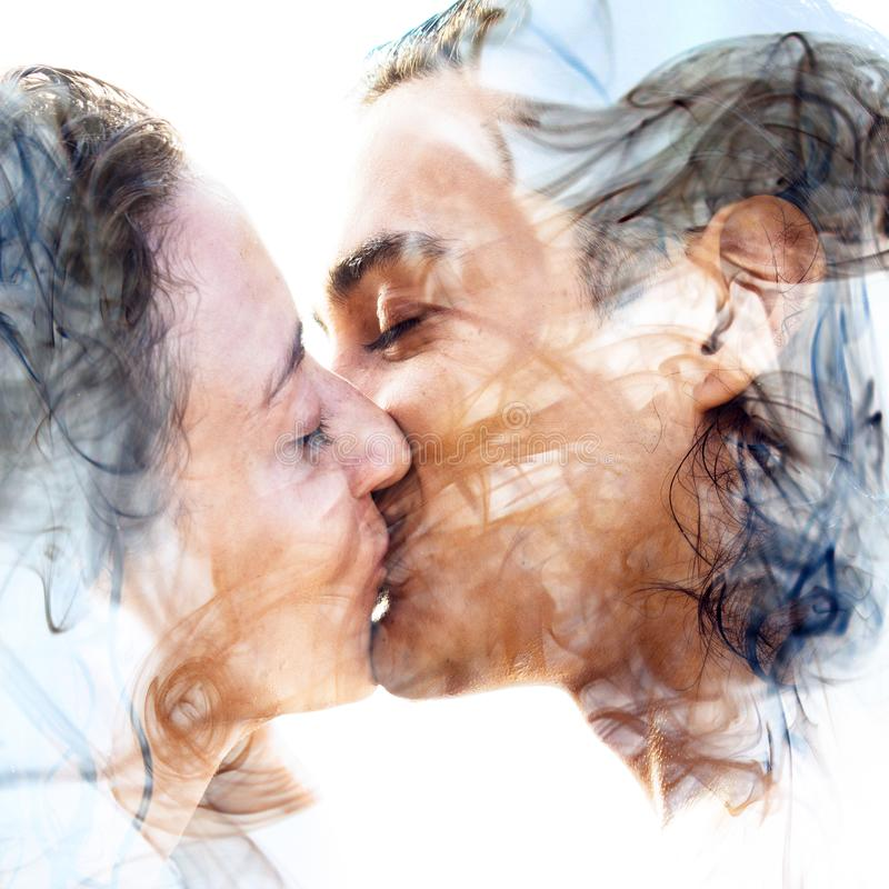 Double exposure of two blissful people close up embracing and be stock image