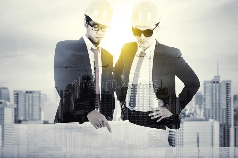 Double exposure of two engineer with blueprint stock photography