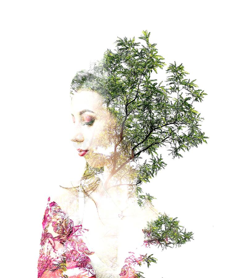 Double exposure of young beautiful girl among the leaves and trees. Portrait of a woman, mysterious look, creative, art, conceptua royalty free stock images