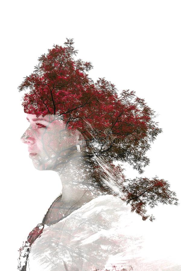 Double exposure of young beautiful girl among the leaves and trees. Portrait of a woman, mysterious look, creative, art, conceptua royalty free stock photography