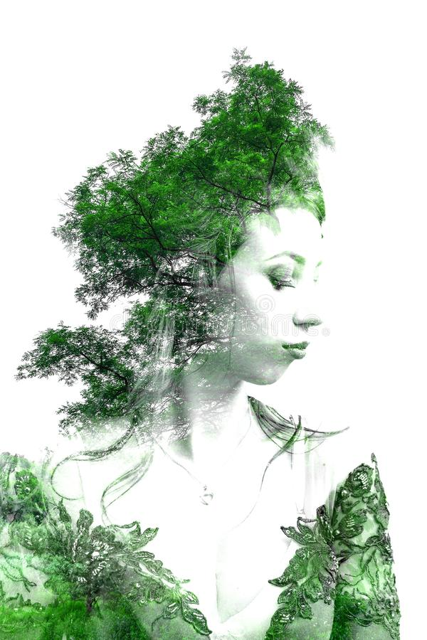 Double exposure of young beautiful girl among the leaves and trees. Portrait of a woman, mysterious look, creative, art, conceptua royalty free stock photo