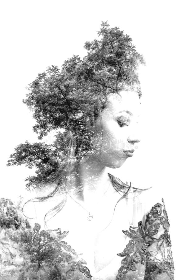 Double exposure of young beautiful girl among the leaves and trees. Portrait of a woman, mysterious look, creative, art, conceptua stock photo