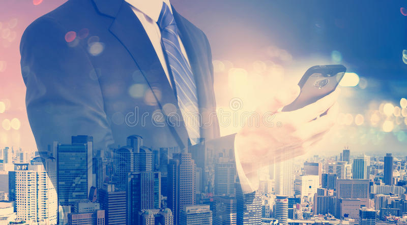 Double exposure of young businessman holding a smartphone royalty free stock photo