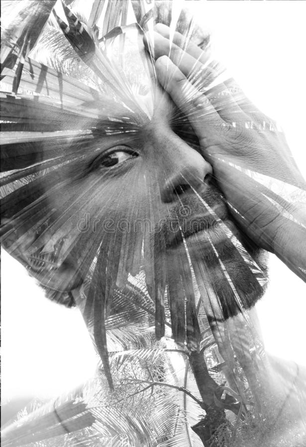 Double exposure of a young handsome man's portrait blended with tropical leaves, showing the perfect beauty of nature`s creatio stock image