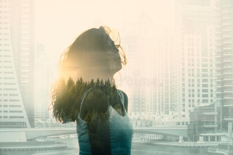 Double exposure with young woman in the modern cityscape and forest royalty free stock images
