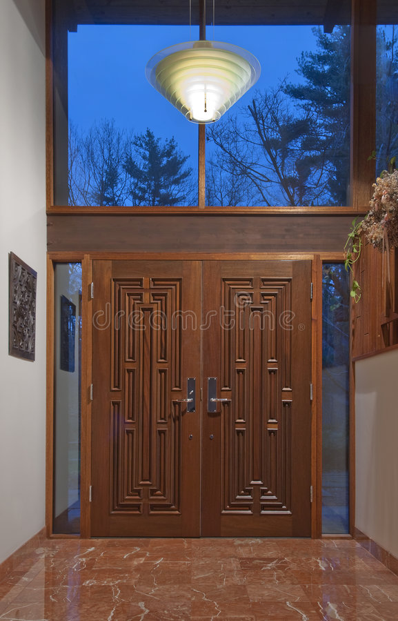 Double front doors in foyer. Two mahogany front doors in marble foyer royalty free stock photo