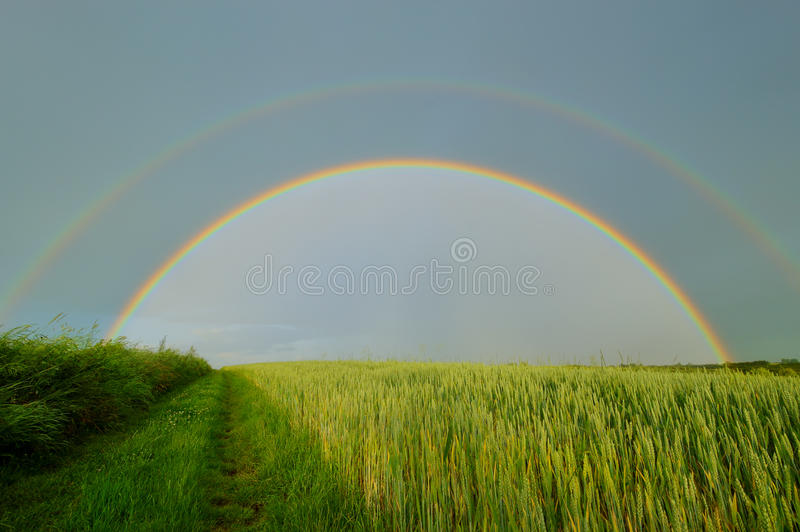 Double full rainbow over country road. Rainbow over blue sky and green field. Late spring, Poland stock image