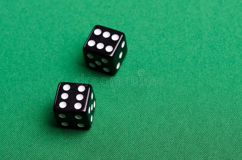Double of gaming bones on a green background. Double of gaming dice on a green background in the studio royalty free stock photo