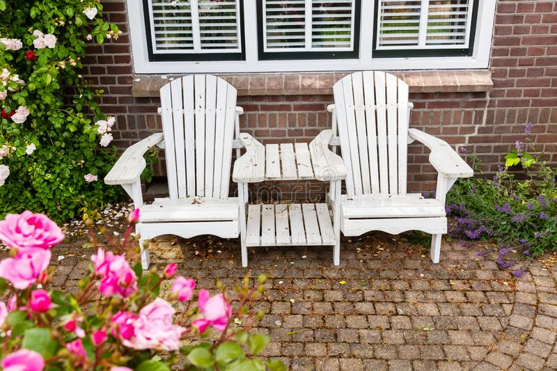 Double garden chair in front of a house. Double garden chair for couples in front of a house stock photography