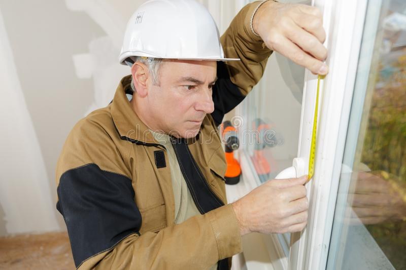 Double glazing installer measuring window. Double glazing installer measuring the window stock photos