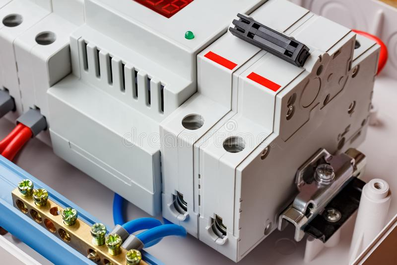 Double input automatic circuit breaker and voltage limiter closeup in the white plastic mounting box royalty free stock photo