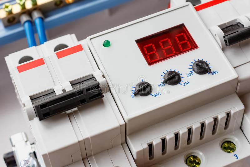 Double input automatic circuit breaker and voltage limiter closeup in the white plastic mounting box stock photography