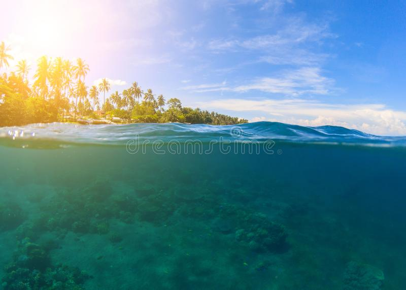 Double landscape with blue sea and sky. Seascape split photo. Double seaview. Underwater coral reef. Above and below waterline. Exotic seashore. Coral reef and stock images