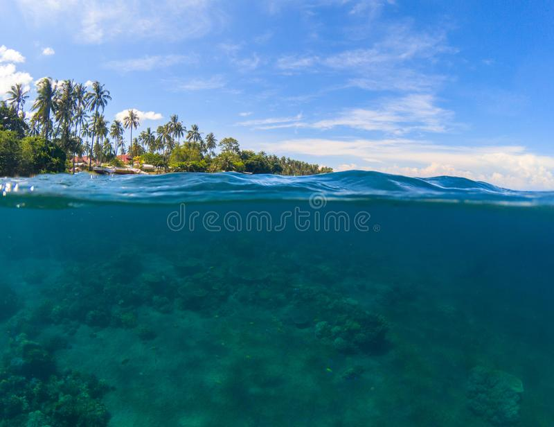 Double landscape. Blue sea and sky. Seascape split photo. Double seaview. Underwater coral reef. Above and below waterline border. Exotic seashore. Coral reef royalty free stock photo