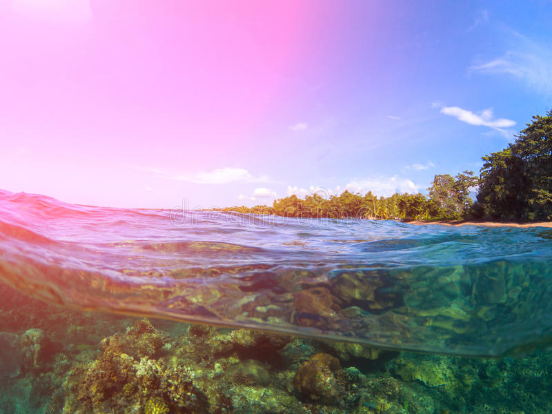 Double landscape with sea and sky. Sea panorama split photo. Tropical island lagoon. Underwater coral reef. Above and below waterline sea view. Exotic seashore stock photos