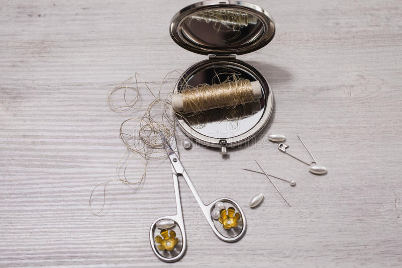 Double mirror, nail clippers, golden thread, pins, needles and sewing items. White beads on a light wooden, background, work of seamstresses stock photo