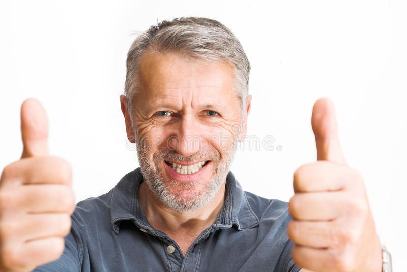 Double optimist. Graying man rises both thumbs with a wide, bright smile royalty free stock photos
