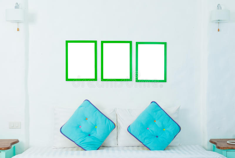 Double oreiller coloré dans la chambre à coucher avec le cadre de photo photographie stock