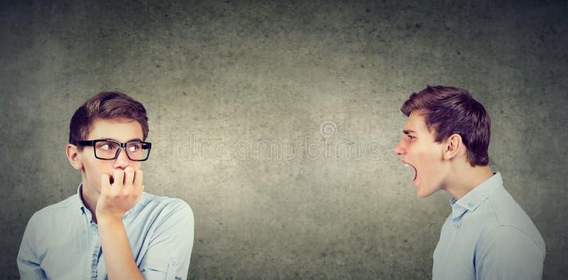 Double personnalité Jeune homme fâché criant à soucieux effrayé lui-même image libre de droits
