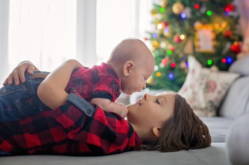 Double portrait of boys on christmas, preschool boy, holding his. Little baby brother, lying down on the couch, christmas decoration behind them stock image