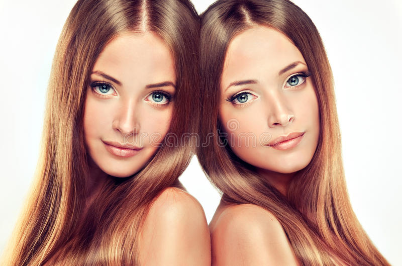 Double portrait of gorgeous twins with ong shiny healthy hair.. Double portrait of gorgeous twins. Clean, fresh skin , delicate make-up and long shiny healthy royalty free stock photography