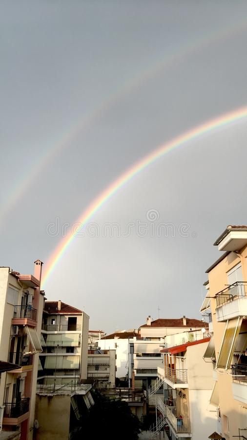 Double rainbow above the houses stock photography