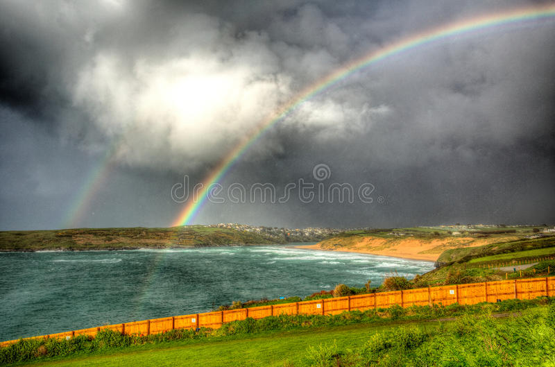 Double rainbow Crantock bay and beach North Cornwall England UK near Newquay in HDR. Two rainbows Crantock bay North Cornwall England UK near Newquay in royalty free stock images