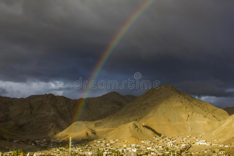 A double rainbow in the dark evening sky over the village in a mountain desert valley royalty free stock photos