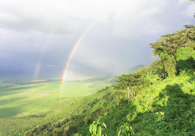 Double rainbow. Magical moment looking into the Ngorongora Crater after a rainfall with double rainbows and sunlight lighting the crater royalty free stock image