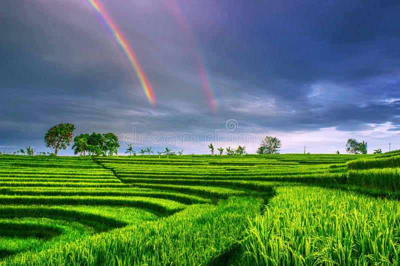 Double rainbow. Morning at mountain with double rainbow on sky with fields stock photo