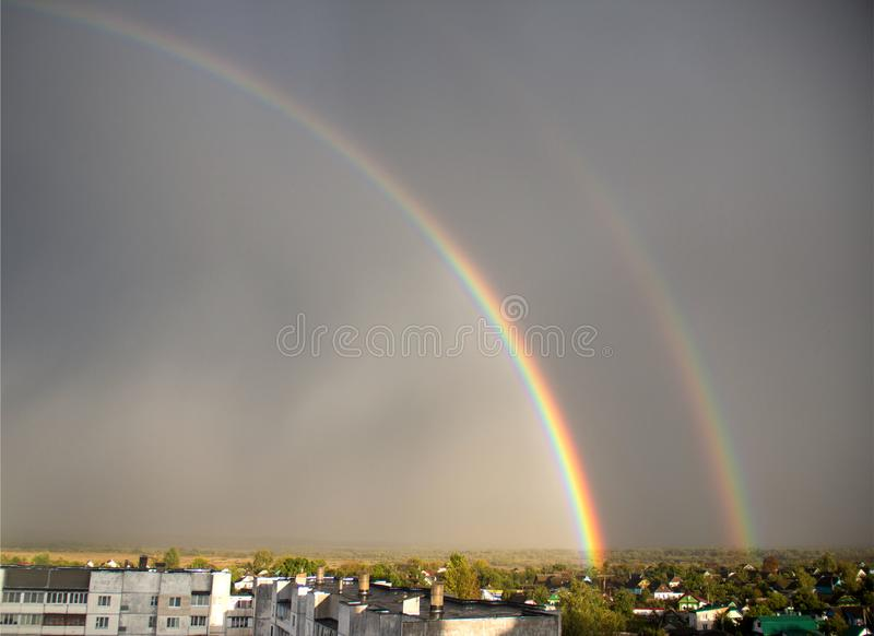Double rainbow over the city, residential area, double rainbow over the blue sky, rainbow stock photo