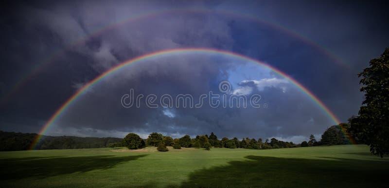 Double rainbow over green fields stock photo