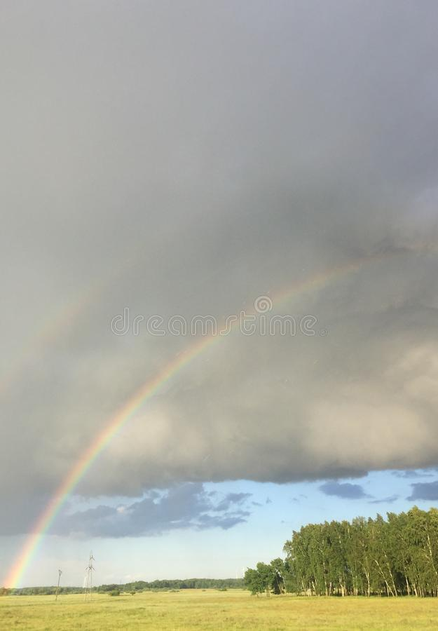 Double rainbow over a meadow royalty free stock photo