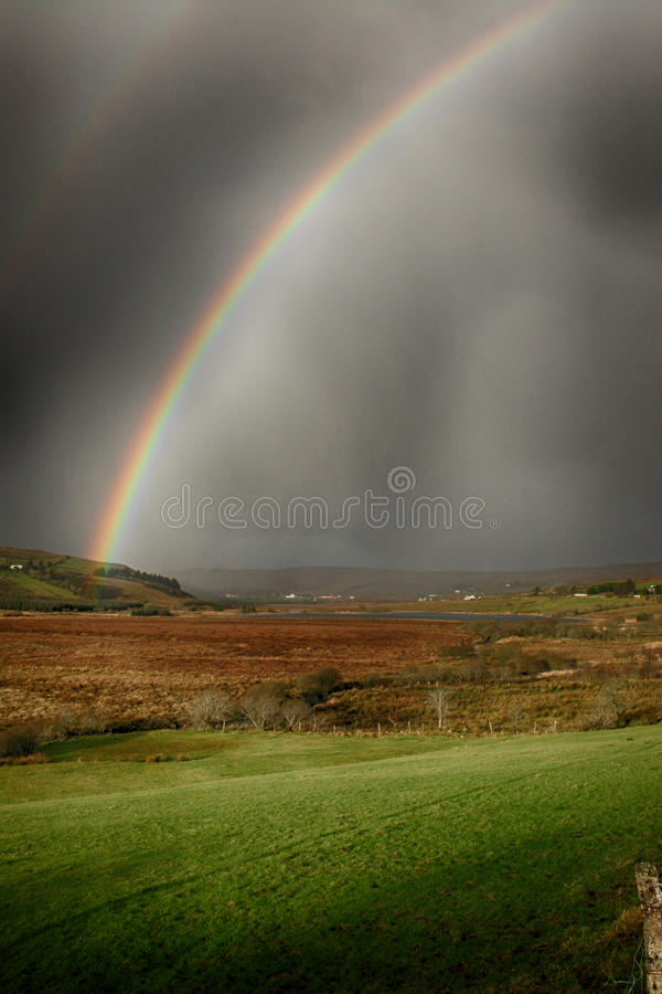 Double rainbow during a storm in Ireland. A double rainbow brightens up a very dark stormy sky in the hills of Donegal, Ireland royalty free stock images