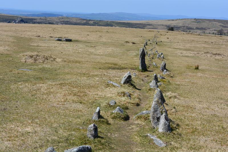 Double row of standing stones on Dartmoor, Merrivale, UK. A stone row, one of the features in the Merrivale Prehistoric Site dating to the Bronze Age, near royalty free stock images