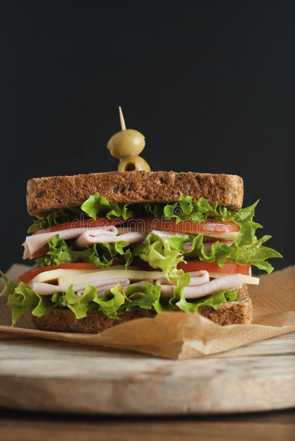 Double sandwich with ham, cheese, lettuce, tomato and green olives. Whole grain bread. Snack or take away food. Black background. royalty free stock image